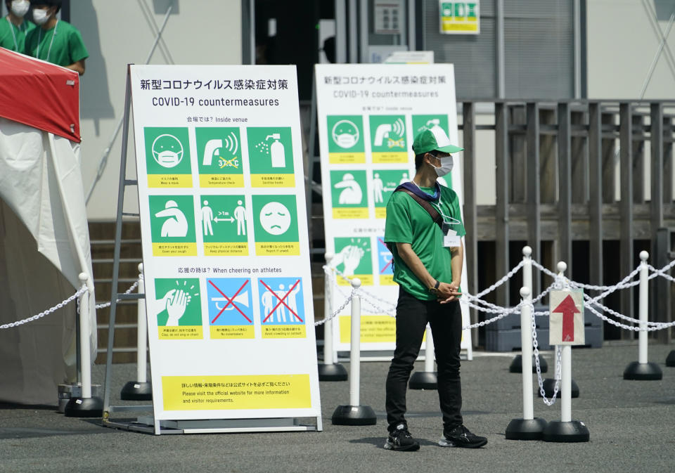 A worker stands in front of a sign describing COVID-19 countermeasures at the Tokyo 2020 Olympics.
