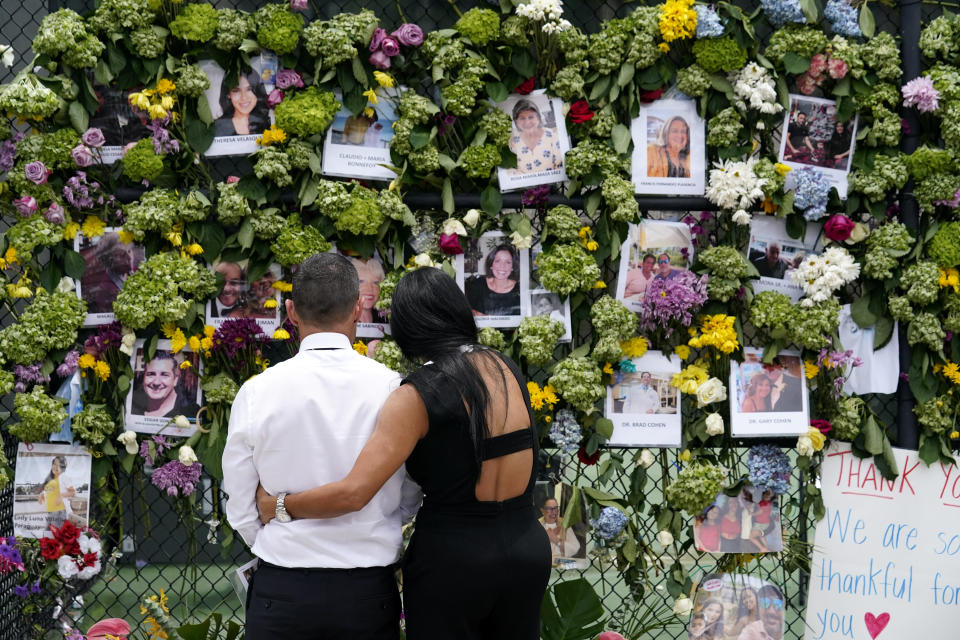 People stand near a make-shift memorial outside St. Joseph Catholic Church near the Champlain Towers South residential condo, Tuesday, June 29, 2021, in Surfside, Fla. Many people were still unaccounted for after Thursday's fatal collapse. (AP Photo/Gerald Herbert)