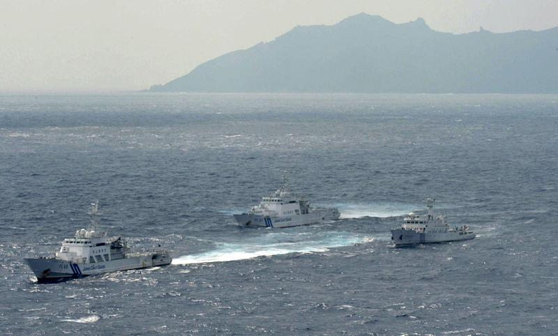 Japan Coast Guard vessels sail along with Chinese surveillance ship Haijian No. 66, right, near disputed islands called Senkaku in Japan and Diaoyu in China, seen in background, in the East China Sea, on Monday, Sept. 24, 2012. (AP Photo/Kyodo News) JAPAN OUT, MANDATORY CREDIT, NO LICENSING IN CHINA, HONG KONG, JAPAN, SOUTH KOREA AND FRANCE