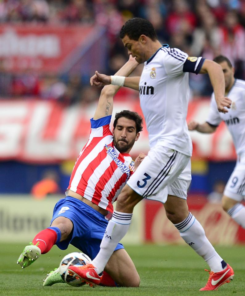 Atletico Madrid's midfielder Raul Garcia (L) vies with Real Madrid's Portuguese defender Pepe during the Spanish league football match Club Atletico de Madrid vs Real Madrid CF at the Vicente Calderon stadium in Madrid on April 27, 2013.   AFP PHOTO/ JAVIER SORIANOJAVIER SORIANO/AFP/Getty Images