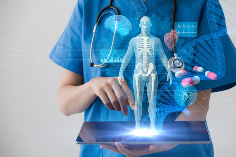 A holographic image of a transparent human being projected from a tablet held by a doctor in scrubs