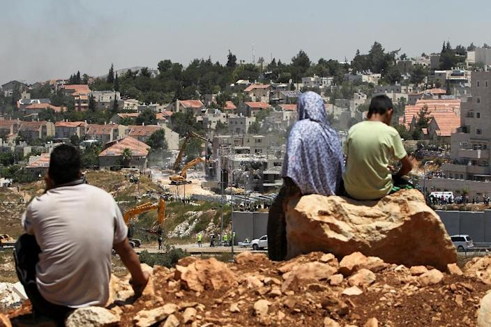 Palestinians from the Jalazoun refugee camp watch bulldozers demolishing the so-called Dreinoff buildings under an Israeli High Court ruling, in the settlement of Beit El on July 29, 2015 (AFP Photo/Abbas Momani)