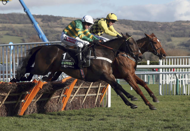 Race winner Buveur D'Air ridden by Barry Geraghty, foreground, clears the last hurdle alongside Melon, ridden by Paul Townend, as they race to finish-line in the Champion Hurdle at Cheltenham Racecourse, Cheltenham England Tuesday March 13, 2018. (David Davies/PA via AP)