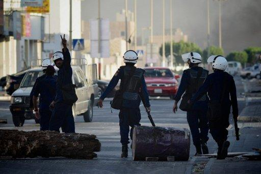 A Bahraini riot policeman flashes the victory sign during clashes with Shiite protesters on the outskirts of Manama