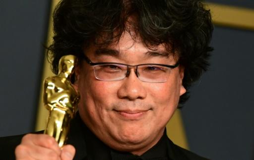 """""""Parasite"""" director Bong Joon-ho poses with one of the four Oscars his film won on a historic night for foreign language cinema"""