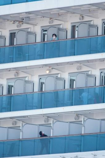 Two passengers in face masks on their balconies aboard the Diamond Princess