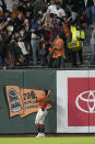 San Francisco Giants left fielder Thairo Estrada watches as fans try to catch the ball on a home run by Houston Astros' Jose Altuve during the fifth inning of a baseball game Friday, July 30, 2021, in San Francisco. (AP Photo/Tony Avelar)