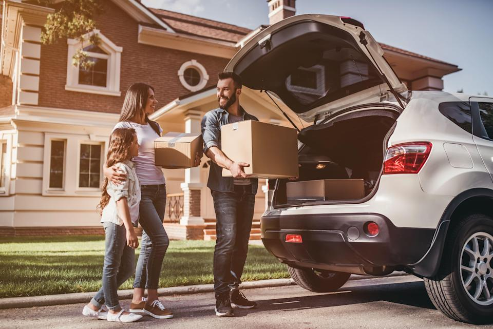 Happy family is standing near car with cardboard boxes. Moving day.