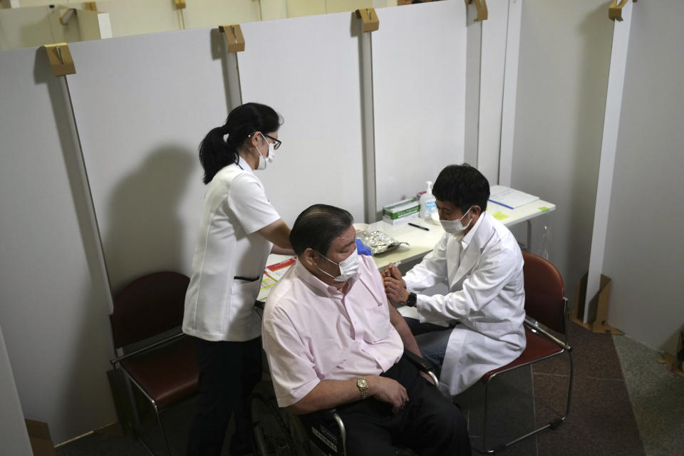 Sumo stable master Nishikijima, left, receives his first dose of Pfizer's COVID-19 vaccine at the Ryogoku Kokugikan sporting arena, in Tokyo on Monday May 24, 2021. The arena, mainly used for sumo wrestling tournaments, is used as temporary inoculation venue for local residents age over 65 years old.(AP Photo/Eugene Hoshiko)