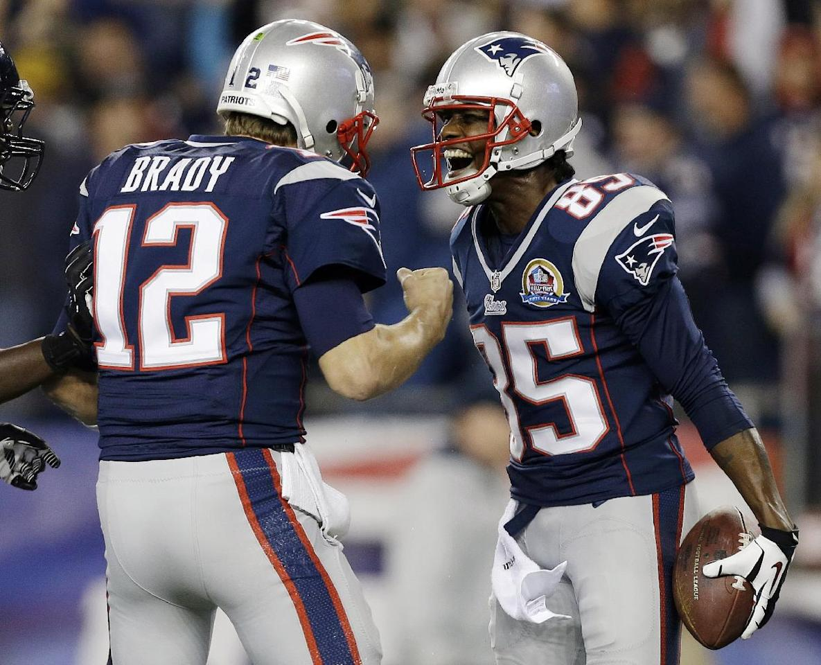 New England Patriots quarterback Tom Brady (12) celebrates his 37-yard touchdown pass to wide receiver Brandon Lloyd (85) during the first quarter of an NFL football game against the Houston Texans in Foxborough, Mass., Monday, Dec. 10, 2012. (AP Photo/Elise Amendola)