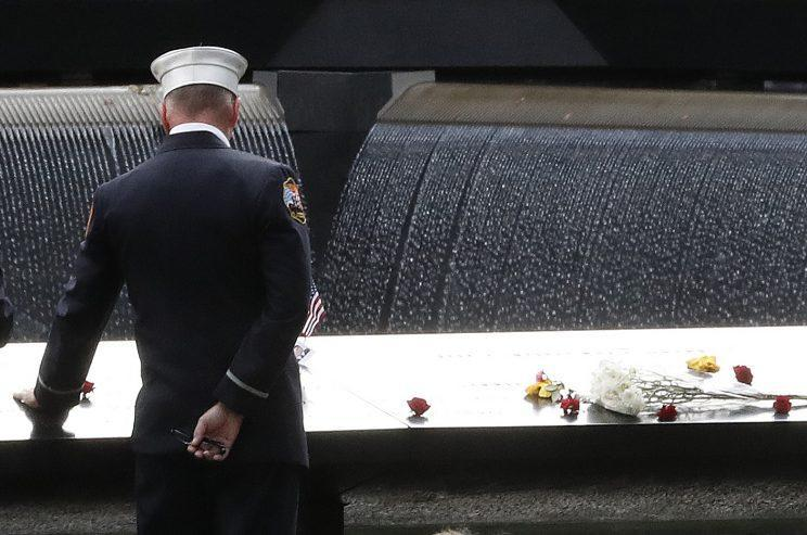 A firefighter touches the names of firefighters carved into the south pool during 15th anniversary ceremony of the attacks on the World Trade Center at the Sept. 11 memorial in New York City. (Photo: Mary Altaffer/AP)