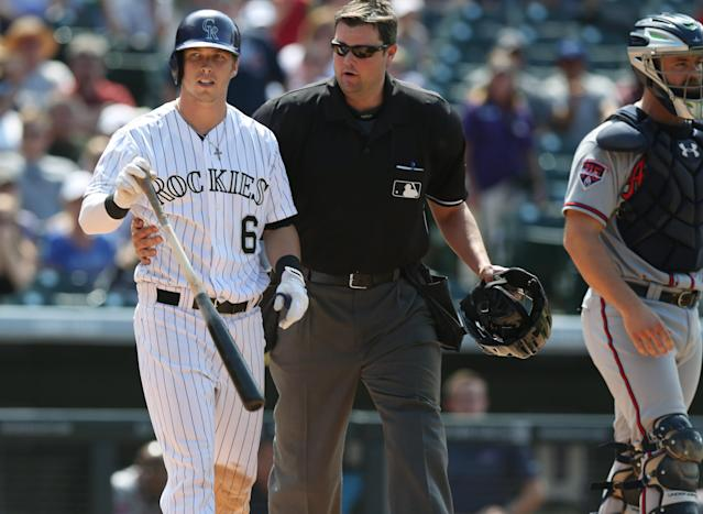 Colorado Rockies' Corey Dickerson, left, is restrained by home plate umpire Jordan Baker as he walks Dickerson down the first-base line after he was hit by a pitch thrown by Atlanta Braves relief pitcher David Carpenter in the eighth inning of the Rockies' 10-3 victory in a baseball game in Denver on Thursday, June 12, 2014. Braves catcher Evan Gattis, right, looks on. Rockies manager Walt Weiss was ejected for arguing over Dickerson being hit by the pitch. (AP Photo/David Zalubowski)