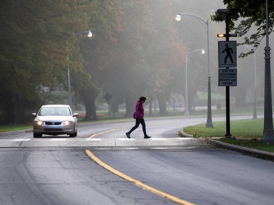 A pedestrian crosses Queen Elizabeth Driveway near Dows Lake as heavy fog blankets Ottawa in early October, 2021. On Sunday, health officials in the nation's capital reported 58 new cases of COVID-19.  (Justin Tang/The Canadian Press - image credit)