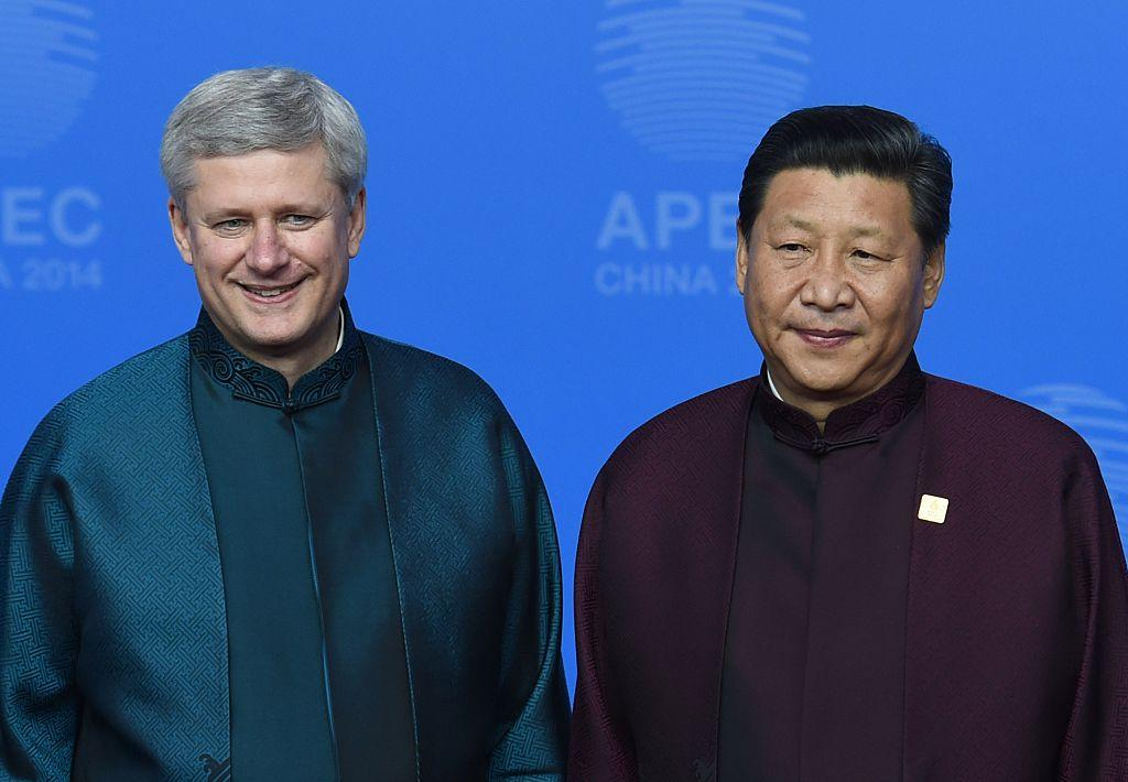 <p>Former Prime Minister Stephen Harper, left, poses with Chinese President Xi Jinping upon arrival for Asia-Pacific Economic Cooperation Summit banquet at the Beijing National Aquatics Center in the Chinese capital on Nov. 10, 2014. Photo by Greg Baker/AFP/Getty Images. </p>