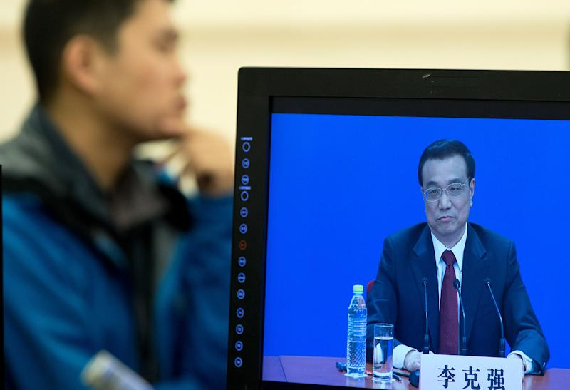 A man listens to a news conference by newly-appointed Premier Li Keqiang who appears on a monitor screen after the closing ceremony of the National People's Congress at the Great Hall of the People in Beijing Sunday, March 17, 2013. China's new leaders pledged to run a cleaner, more efficient government and slash spending on official perks Sunday as the ceremonial legislature wrapped up a pivotal session to install a new leadership in a once-a-decade transfer of power. (AP Photo/Andy Wong)