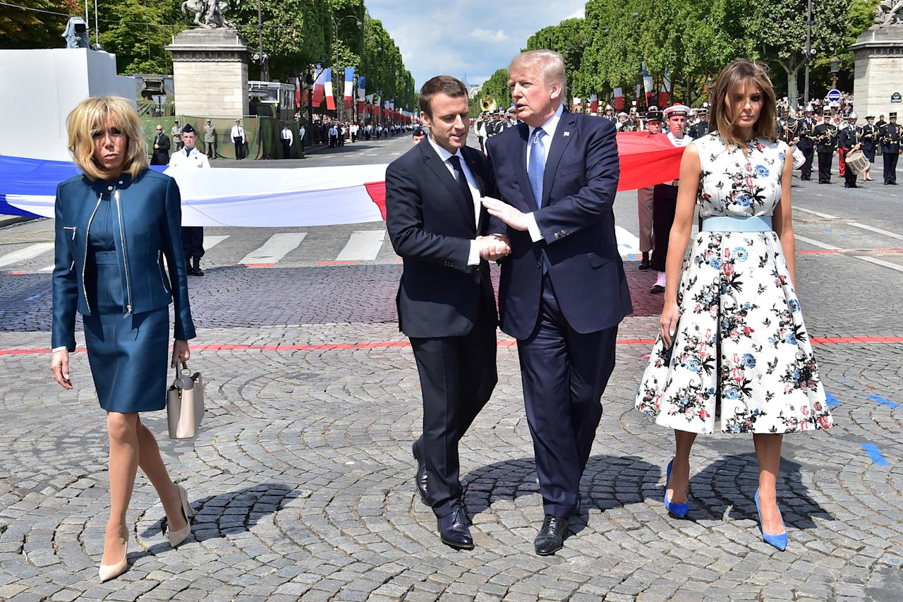 <p>French President Emmanuel Macron (2nd L) shakes hands with President Donald Trump, next to Macron's wife Brigitte Macron (L) and First Lady Melania Trump during the traditional Bastille Day military parade on the Champs-Elysees avenue in Paris, France, July 14, 2017. (Photo: Christophe Archambault/Pool/Reuters) </p>