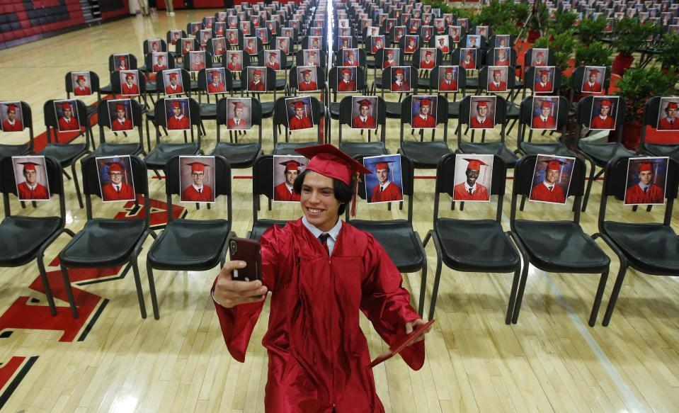 Paul Santiago Kelley, a graduating senior at Brophy College Preparatory, smiles as he takes a selfie as he celebrates Diploma Days with photos of all his fellow classmates after getting his diploma, due to the coronavirus on May 28, 2020, in Phoenix. (AP Photo/Ross D. Franklin)