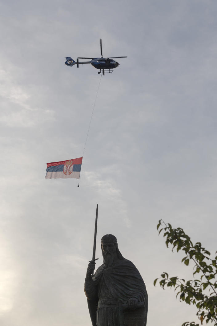 """A helicopter carries the flag of Serbia as it passes the collosal monument to Stefan Nemanja, a Serbian medieval ruler, during a ceremony to mark the newly established """"Day of Serb Unity, Freedom and the National Flag"""" state holiday in Belgrade, Serbia, Wednesday, Sept. 13, 2021. Serbia has kicked off a new holiday celebrating national unity with a display of military power, triggering unease among its neighbors. (AP Photo/Marko Drobnjakovic)"""