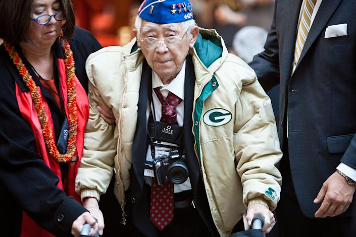 A Japanese-American veteran of the 100th Infantry Battalion, 442 Regimental Combat Team is escorted at a ceremony in which they, along with veterans of the Military Intelligence Service, United States Army, received the Congressional Gold Medal in recognition of dedicated service during World War II on November 2, 2011 in Washington, DC. About 19,000 veterans were awarded the honor, which is Congress' highest civilian medal. (Photo by Brendan Hoffman/Getty Images)