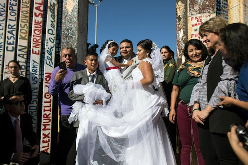 Bride Evelia Reyes and groom Brian Houston pose for pictures after marrying at an open gate on the US-Mexico border at Playas de Tijuana, Mexico
