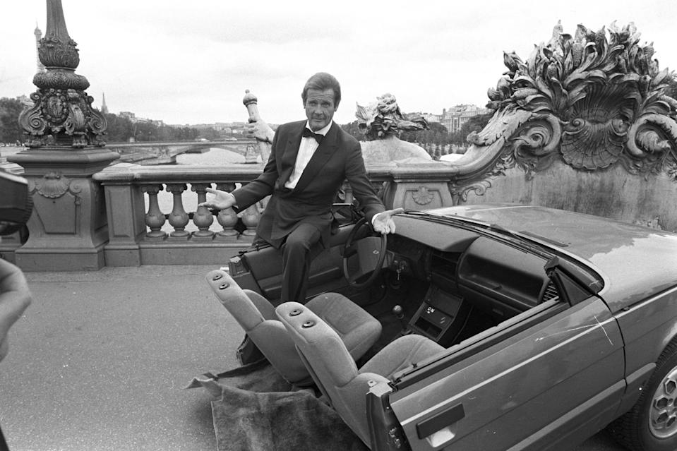 """British actor Roger Moore on set of the <a href=""""https://www.cntraveler.com/galleries/2015-01-07/50-best-travel-films-of-the-past-50-years?mbid=synd_yahoo_rss"""" rel=""""nofollow noopener"""" target=""""_blank"""" data-ylk=""""slk:James Bond movie"""" class=""""link rapid-noclick-resp"""">James Bond movie</a> <em>A View to a Kill</em> with half a car during filming in Paris."""