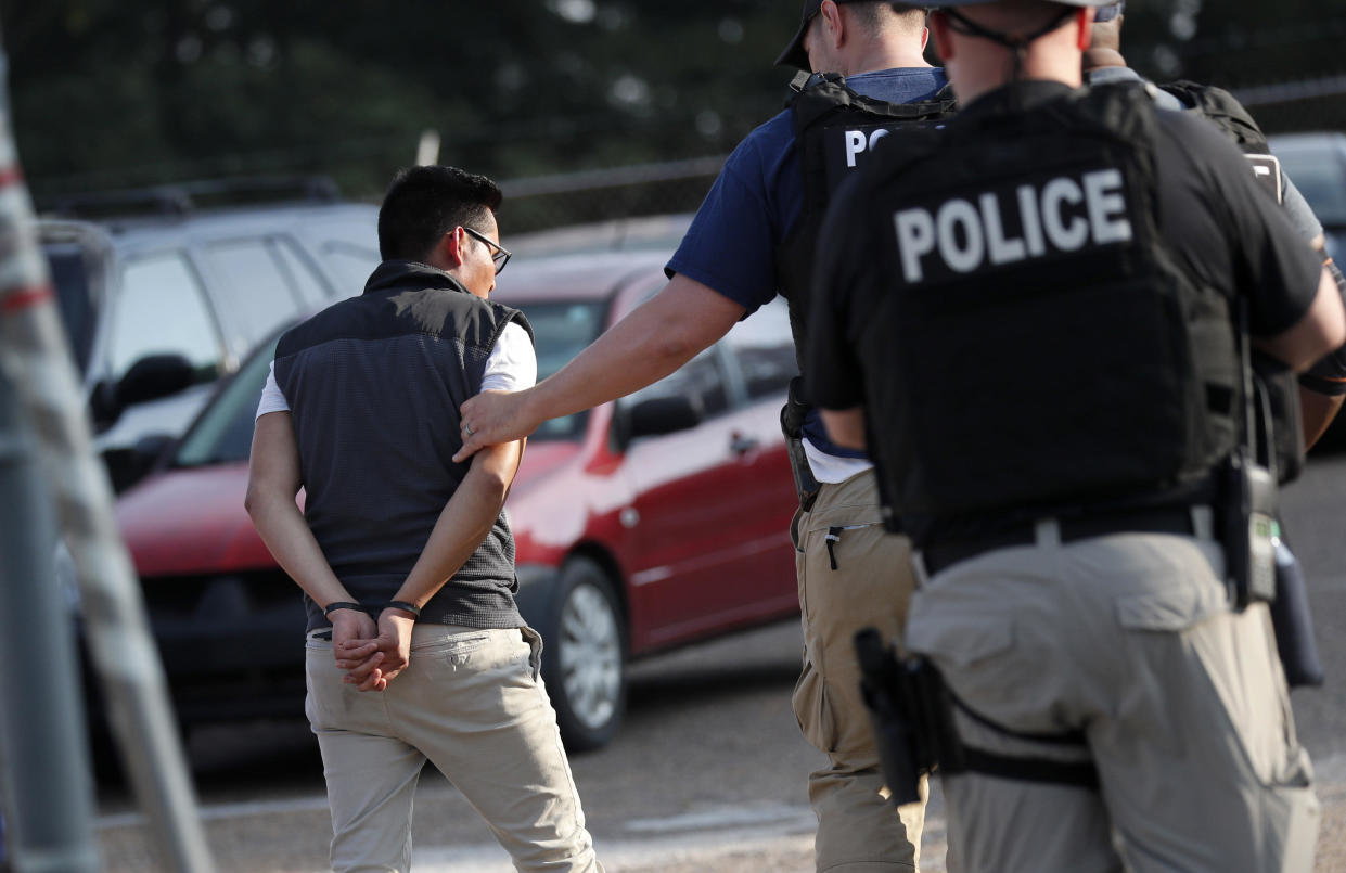 A man is taken into custody at a Koch Foods Inc. plant in Morton, Mississippi, on Wednesday, August 7, 2019. / Credit: Rogelio V. Solis / AP