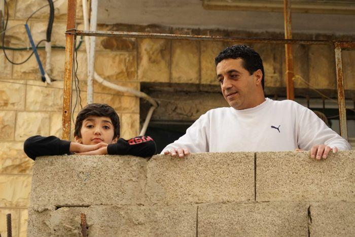 A small boy and a man on a balcony