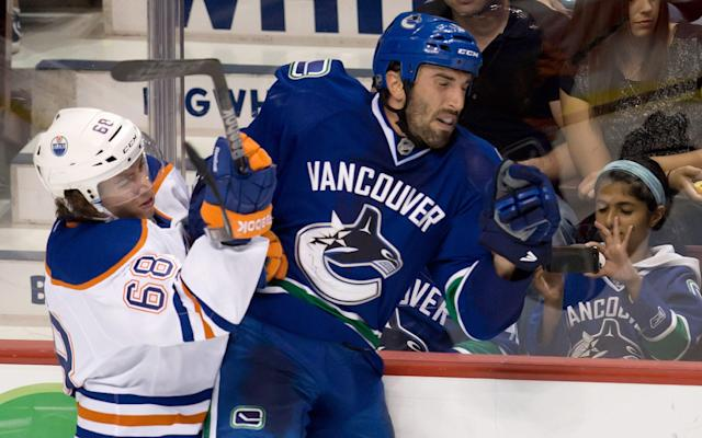 Edmonton Oilers' Tyler Pitlick, left, checks Vancouver Canucks' Jason Garrison during the second period of a preseason NHL hockey game Wednesday, Sept. 18, 2013, in Vancouver, British Columbia. (AP Photo/The Canadian Press, Darry Dyck)