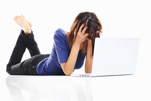 C50YCX Frustrated young girl in angry mood with laptop lying on white surface