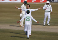Pakistan's Sheheen Afridi, center, celebrates with teammate Fawad Alam after taking the wicket of South Africa's Dean Elgar during the fourth day of the second cricket test match between Pakistan and South Africa at the Pindi Stadium in Rawalpindi, Pakistan, Sunday, Feb. 7, 2021. (AP Photo/Anjum Naveed)