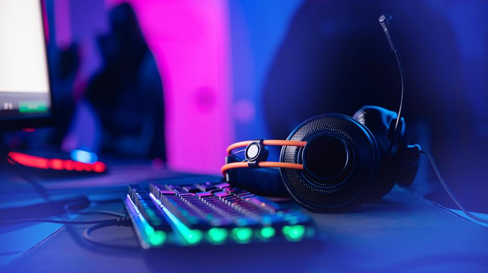 Professional headphones with microphone for video games and cyber sports gaming monitor in neon color blur background.
