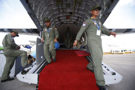 Indonesian airforce personnel tidy up their CN235-220 maritime surveillance aircraft displayed at the Singapore Airshow at Changi Exhibition Center February 17, 2016. Picture taken February 17, 2016. REUTERS/Edgar Su