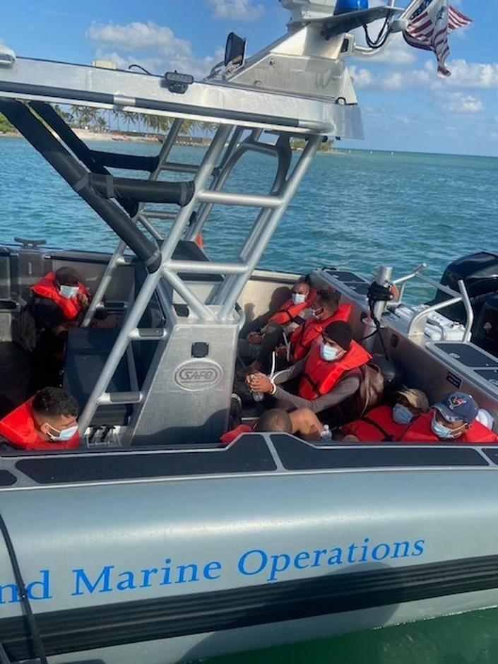 A group of Cuban men who were caught by Border Patrol agents after they landed in the Florida Keys Friday, April 9, 2021, sit handcuffed in the back of a U.S. Customs and Border Protection Air and Marine Operations boat.