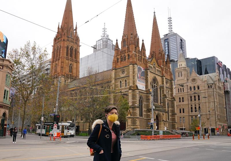A woman walks past St Paul's Cathedral while wearing a face mask as a preventive measure against the spread of novel coronavirus COVID-19 in Melbourne, Sunday, June 21, 2020.