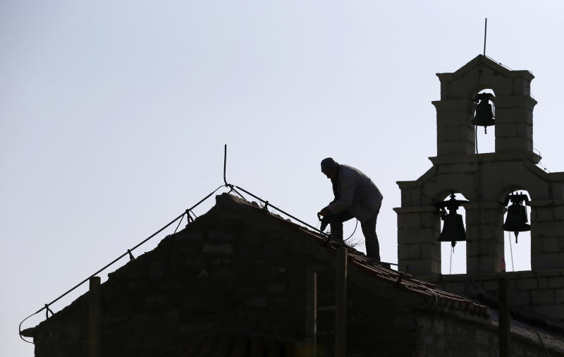 In this photo taken Wednesday, March 15, 2017, a worker repairs roof on Holy Sunday church in the 'Tsar's Village' complex near Sveti Stefan peninsula in Montenegro. Russian tourists are flocking to Montenegro despite warnings from Moscow against their visits to the latest NATO-member country. (AP Photo/Darko Vojinovic)