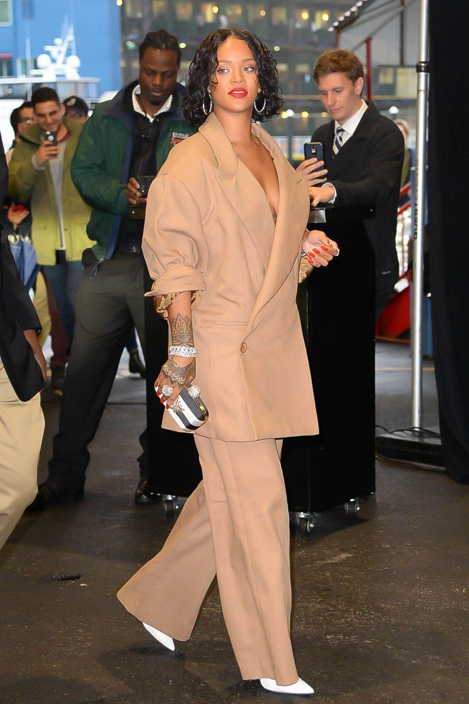 <p>In a custom Matthew Adams Dolan tan suit, striped clutch, white pumps and hoop earrings while out in New York City.</p>