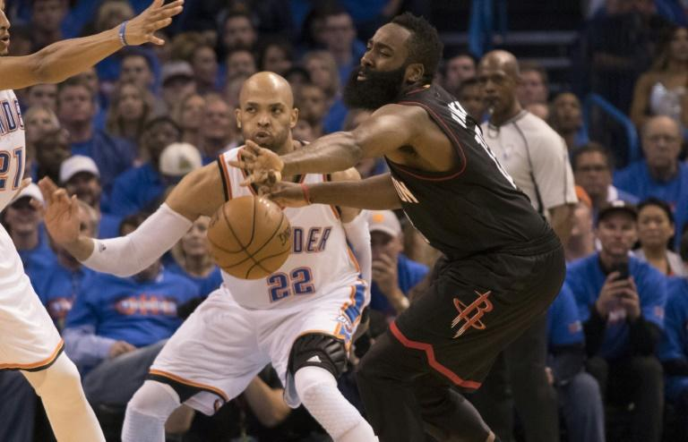 Taj Gibson (C) of the Oklahoma City Thunder forces James Harden of the Houston Rockets to pass the ball during Game Three in the Western Conference Quarterfinals