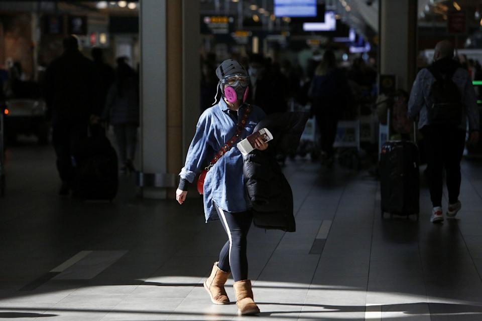 A woman wearing a protective face mask and goggles walks through Vancouver International Airport in Richmond, B.C. on March 16, 2020. (Photo: Jesse Winter / Reuters)