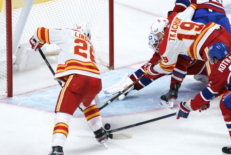 Montreal Canadiens goaltender Jake Allen manages to stop the puck away next to Calgary Flames' Elias Lindholm, left, and Matthew Tkachuk during the second period of an NHL hockey game Friday, April 16, 2021, in Montreal. (Paul Chiasson/The Canadian Press via AP)