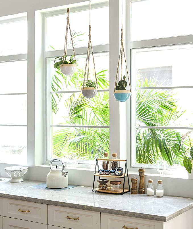 """<h2>Mkono Ceramic Hanging Planter Trio</h2><br>This sweet trio of ceramic planters hanging from simple jute ropes is ready to brighten up a kitchen to living room or bedside corner. <br><br><strong>Mkono</strong> Ceramic Hanging Planter, Set of 3, $, available at <a href=""""https://amzn.to/3e5DZO4"""" rel=""""nofollow noopener"""" target=""""_blank"""" data-ylk=""""slk:Amazon"""" class=""""link rapid-noclick-resp"""">Amazon</a>"""
