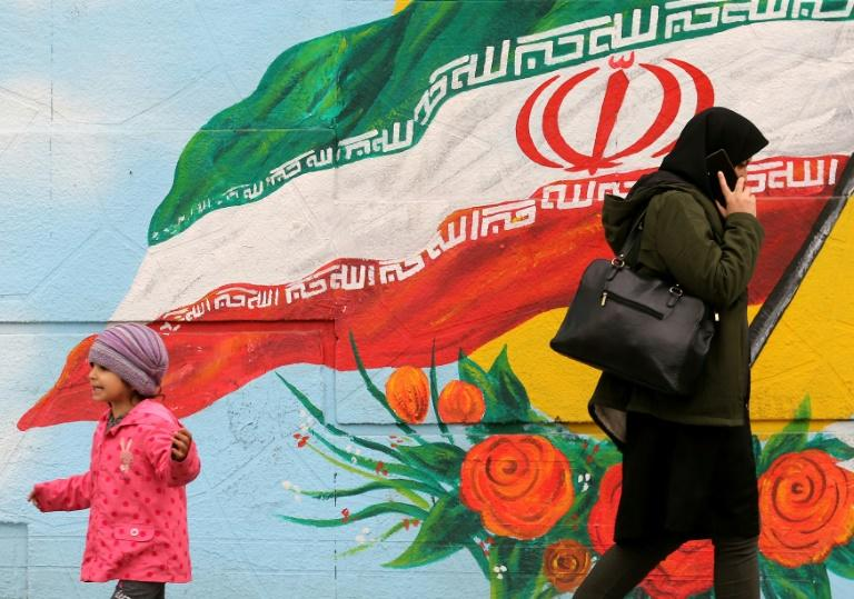 A woman and child walk past a mural with the Iranian national flag in Tehran (AFP Photo/ATTA KENARE)