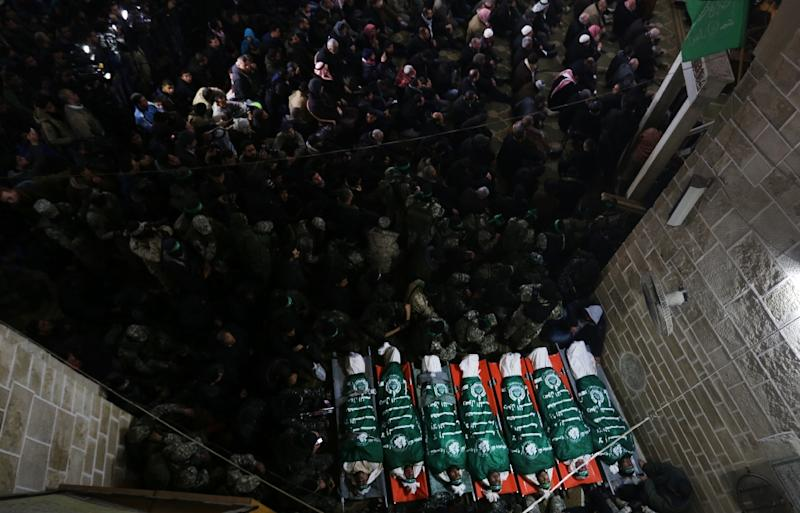Palestinian Hamas militants and mourners gather around the bodies of seven Hamas militants killed after a tunnel, built for fighting Israel, collapsed in the Gaza Strip, during their funeral in Gaza City on January 29, 2016 (AFP Photo/Mahmud Hams)