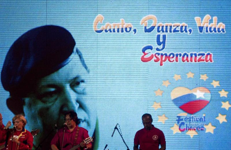 "Musicians perform in front of an image of Venezuela's President Hugo Chavez that reads in Spanish ""singing, dance, life and hope"" during a concert in support of him marking the 8th anniversary of the Bolivarian Alliance for the Americas group, ALBA, in Managua, Nicaragua, Monday Dec. 17, 2012. Chavez is recovering in Cuba from a surgery, his fourth operation related to his pelvic cancer since June 2011. (AP Photo/Esteban Felix)"