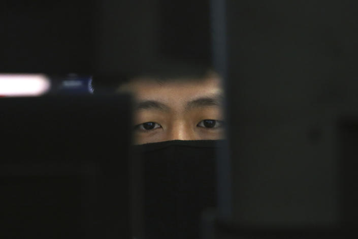 A currency trader wearing a face mask watches monitors at the foreign exchange dealing room of the KEB Hana Bank headquarters in Seoul, South Korea, Tuesday, March 10, 2020. Asian stock markets are taking a breather from recent declines. (AP Photo/Ahn Young-joon)