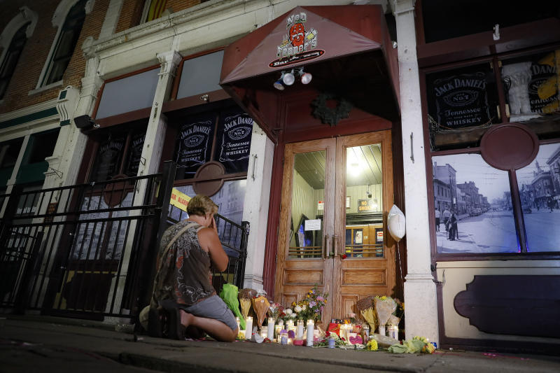 FILE - In this Aug. 4, 2019 file photo, mourners visit a makeshift memorial outside Ned Peppers bar following a vigil at the scene of a mass shooting in Dayton, Ohio. As soon as six Ohio police officers hailed as heroes killed the gunman to end an attack that claimed nine lives in Dayton, police began work to save the wounded. Their at-the-scene aid was the latest example of how police have taken on an increased medical role in mass shootings, among any adjustments in tactics, weapons, equipment and training U.S. law enforcement agencies have made as shootings have mounted. (AP Photo/John Minchillo, File)
