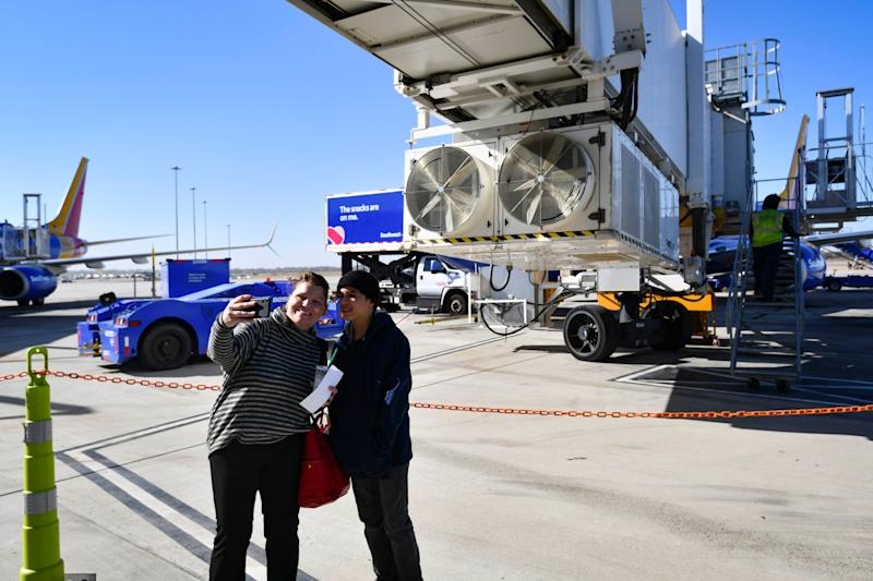 Travelers Karen Meris, left, and son Quinn Meris take a selfie before boarding their Southwest Airlines flight from the back of the aircraft.