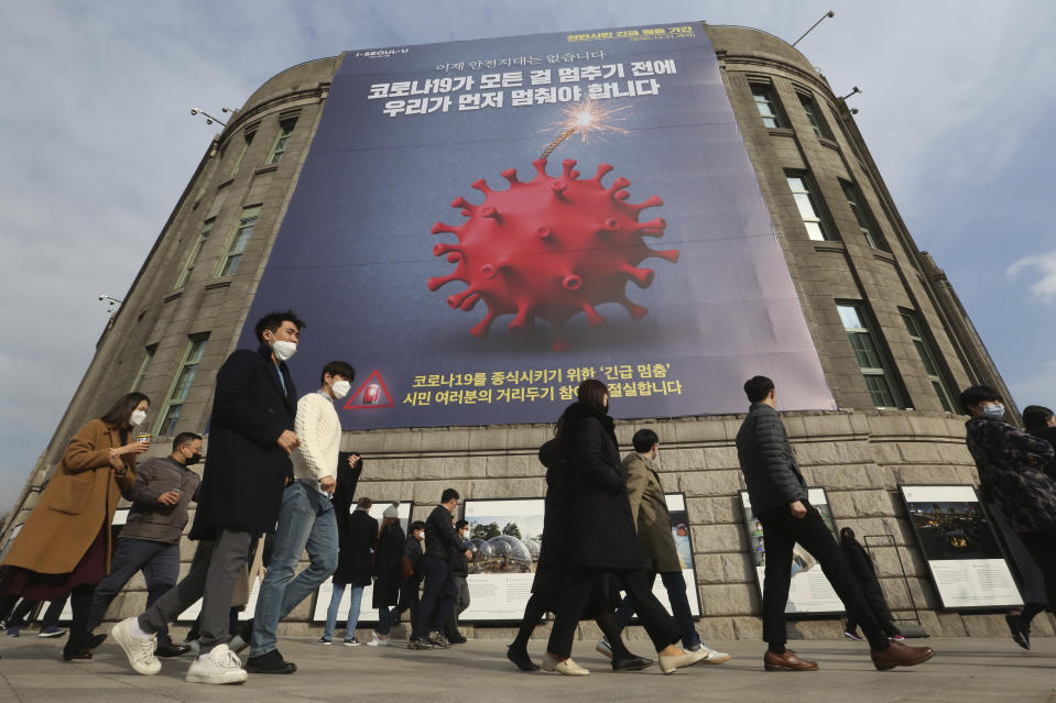 "People wearing face masks as a precaution against the coronavirus walk under a banner emphasizing an enhanced social distancing campaign in front of Seoul City Hall in Seoul, South Korea, Wednesday, Nov. 25, 2020. The banner reads: ""We have to stop before COVID-19 stops everything."" (AP Photo/Ahn Young-joon)"
