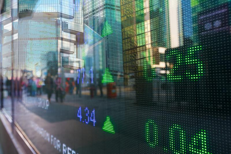 A close-up of an electronic securities market board display on the street; in the reflection, you can see people walking by