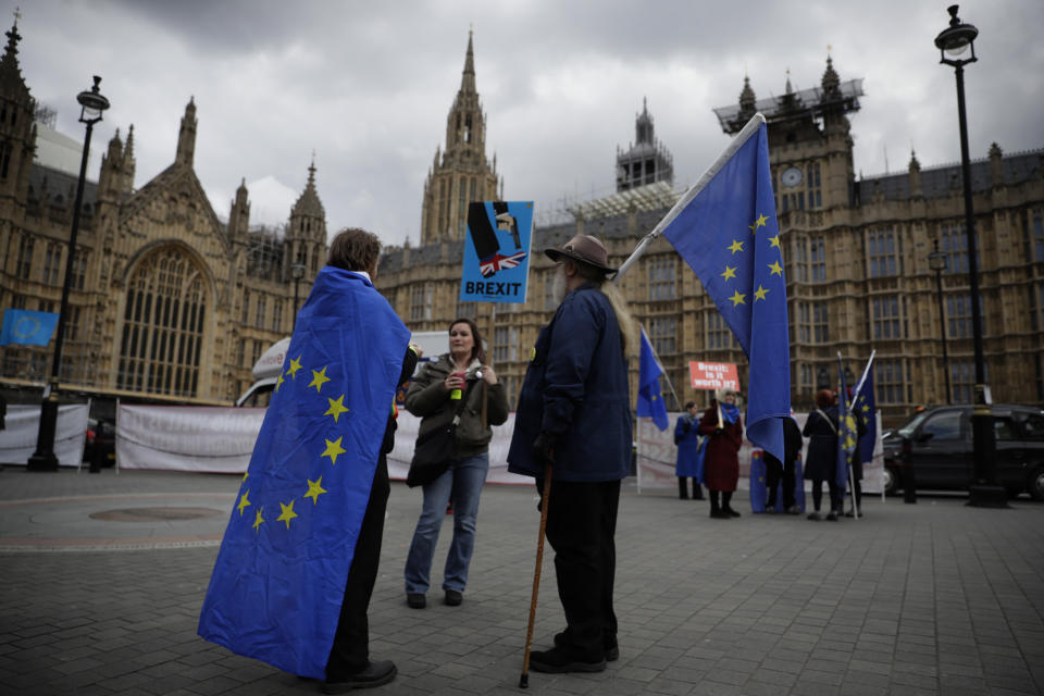Anti-Brexit remain in the European Union supporters protest backdropped by the Houses of Parliament in London, Wednesday, April 3, 2019. After failing repeatedly to win Parliament's backing for her Brexit blueprint, Britain's Prime Minister Theresa May dramatically changed gear Tuesday, saying she would seek to delay Brexit _ again _ and hold talks with the opposition to seek a compromise.  (AP Photo/Matt Dunham)