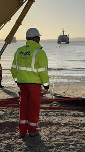 A staff member from Pioneer Consulting supervises the landing of the Southern Cross NEXT cable on the beach in Takapuna, New Zealand.